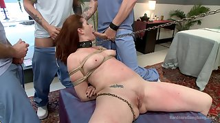 Redhead gets gagged by dicks while sitting tied up in ropes